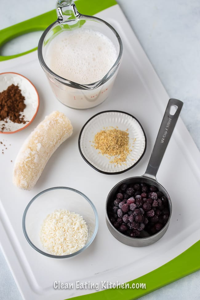 vegan chocolate blueberry smoothie ingredients on a white cutting board