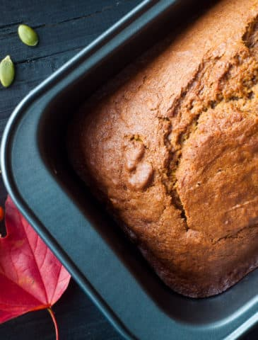 Freshly baked pumpkin bread cake in a baking tin. Served with a scattering of pumpkin seeds and some autumn fall leaves and berries.