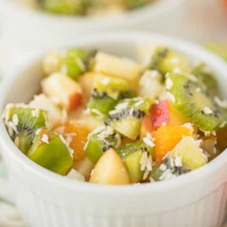 fruit salad in a white bowl with coconut on top