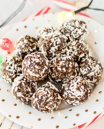chocolate peppermint energy balls on a plate with christmas lights and candy canes