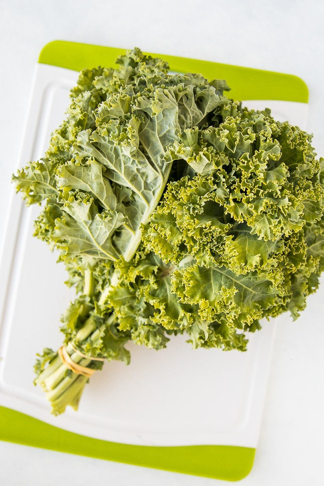 green curly kale bunch on a white board