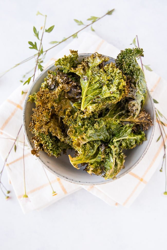 baked kale chips in a bowl on a white and yellow striped towel