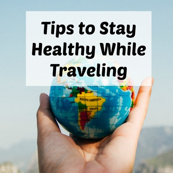 healthy travel tips with hand holding globe