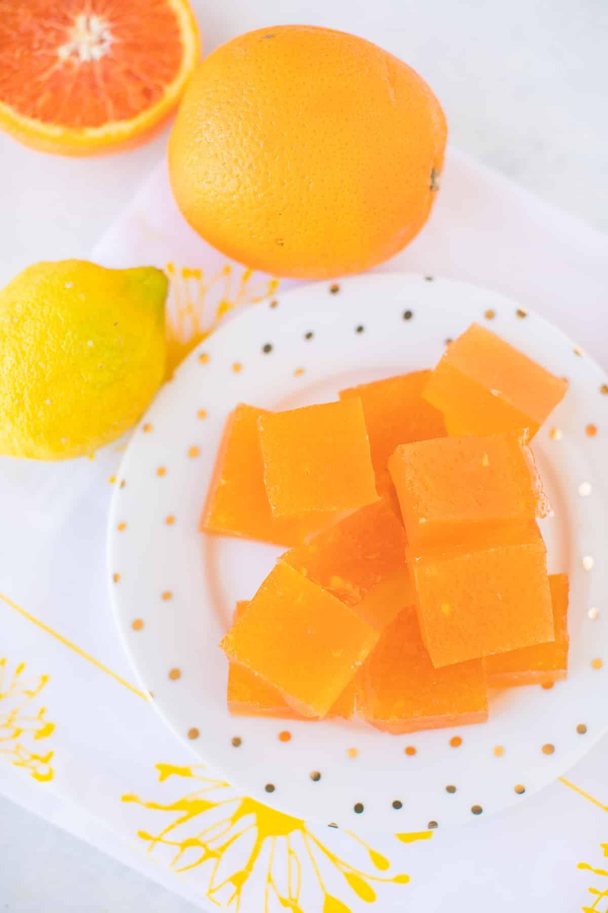 plate of orange jello slices with fresh fruit around