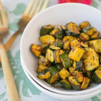 bowl of roasted zucchini with two gold forks