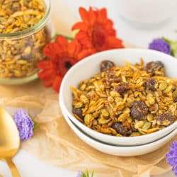 bowl of pumpkin granola with two gold spoons