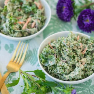 two bowls of kale salad with gold forks and purple flowers