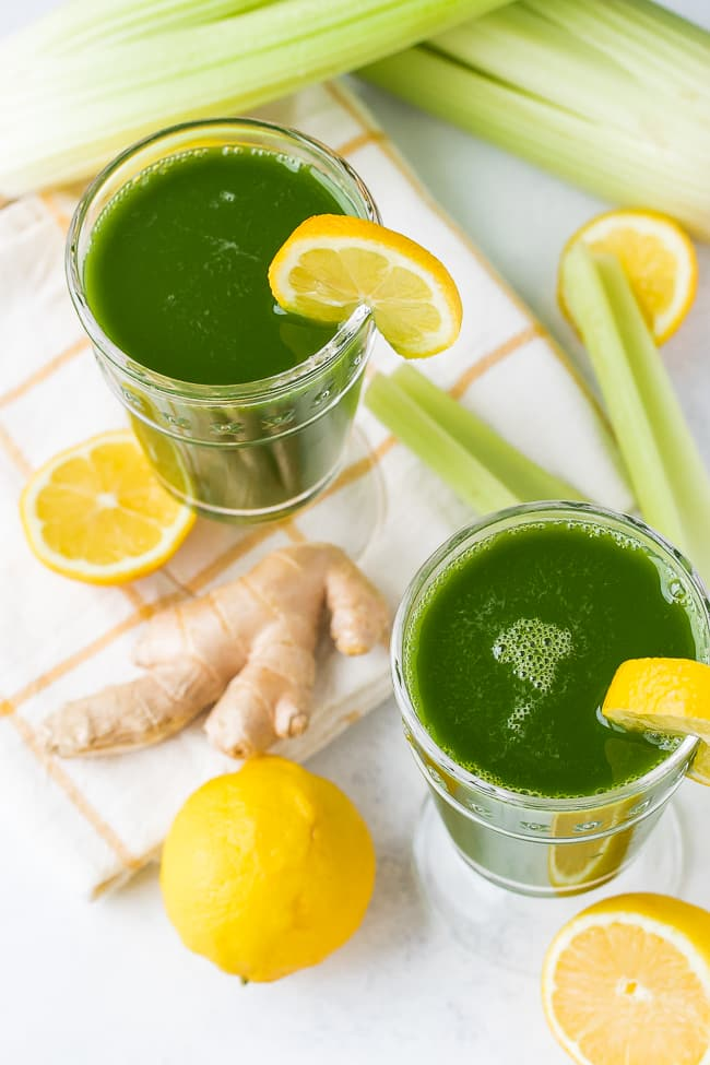 two glasses of green juice with lemon and ginger