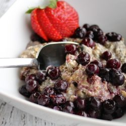 Bowl of oatmeal with blueberries and a strawberry