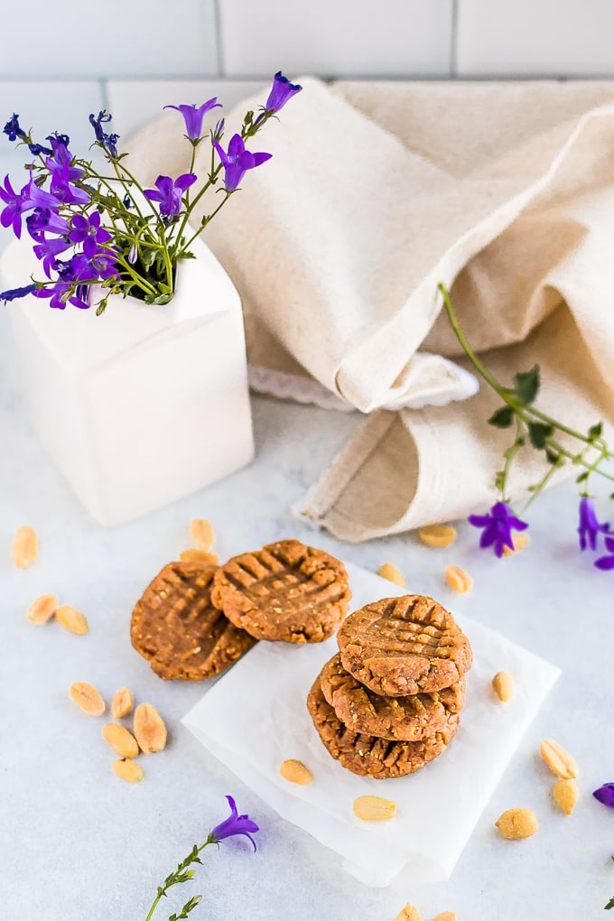 healthy no bake cookies on a white plate with flowers behind