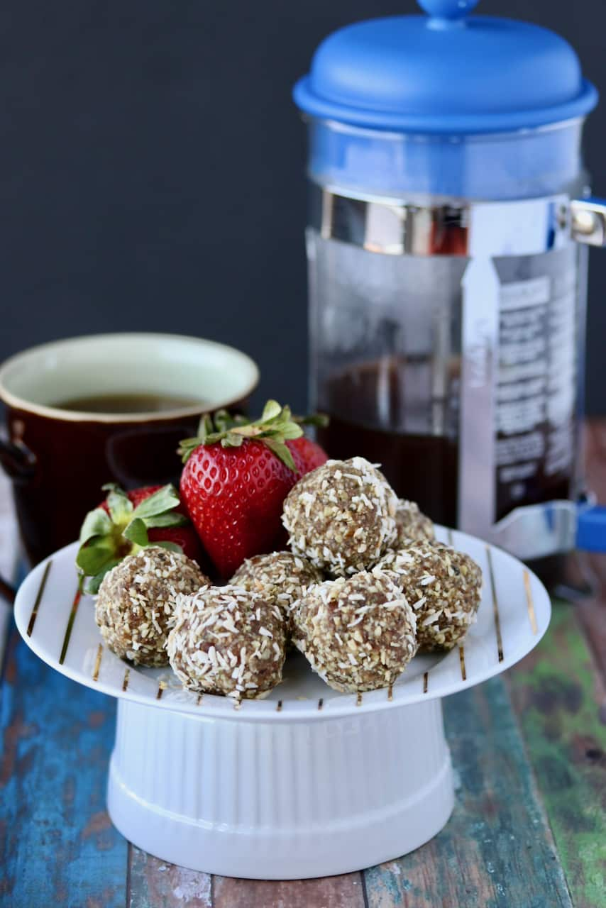 energy balls on a platter with cup of coffee