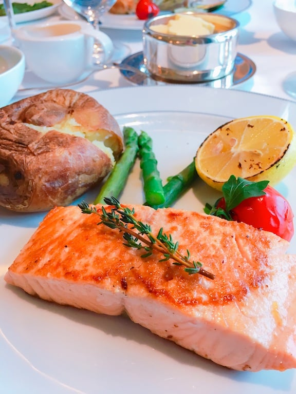 salmon dinner with steamed vegetables and baked potato