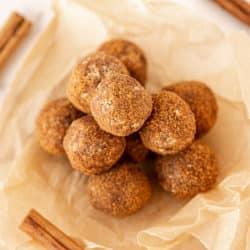 plate of pumpkin spice energy balls with cinnamon sticks