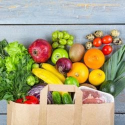 grocery bag with healthy foods coming out the top