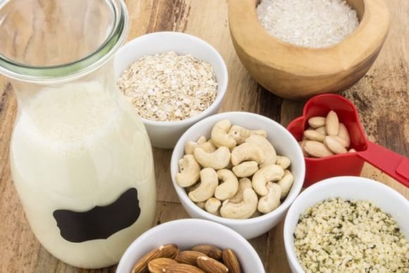 Bottle of homemade plant based milk and bowls with ingredients, on wooden background