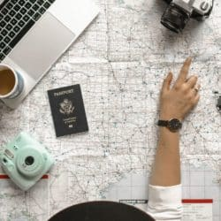 woman looking at map with laptop and passport
