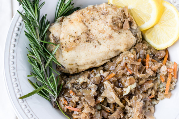 Crockpot chicken thighs in bowl with rosemary, lemon, up close.