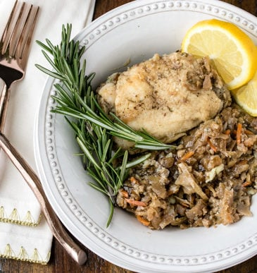 Crockpot chicken thighs in bowl with rosemary, lemon, and silverware on a white napkin