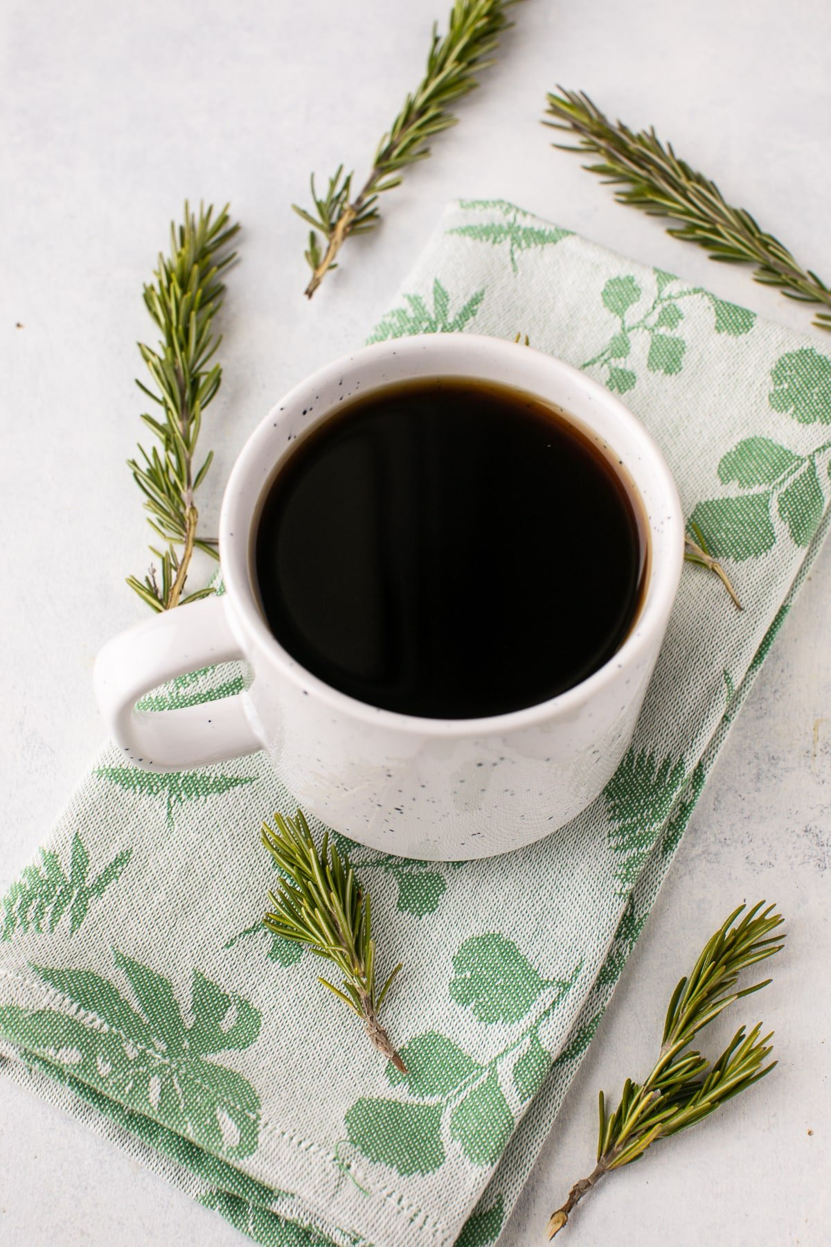 white mug with coffee and sprigs of rosemary on a table