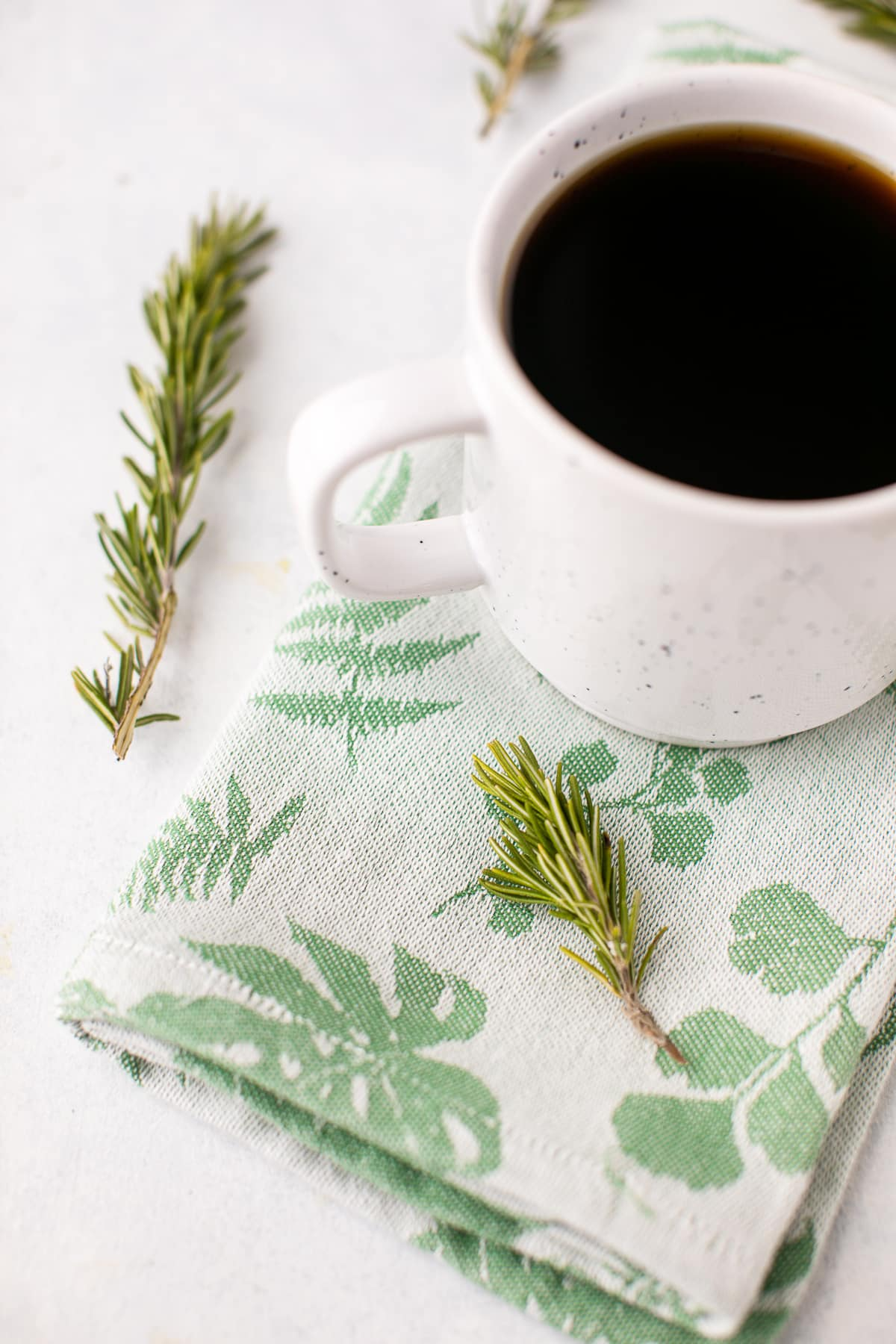 cup of coffee with fresh rosemary sprigs