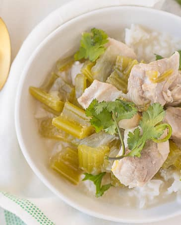 instant pot coconut chicken soup in white bowl with gold spoon