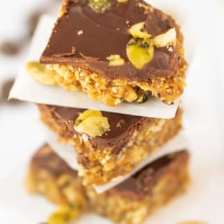 chocolate fig bars stacked on top of each other with parchment paper between each one