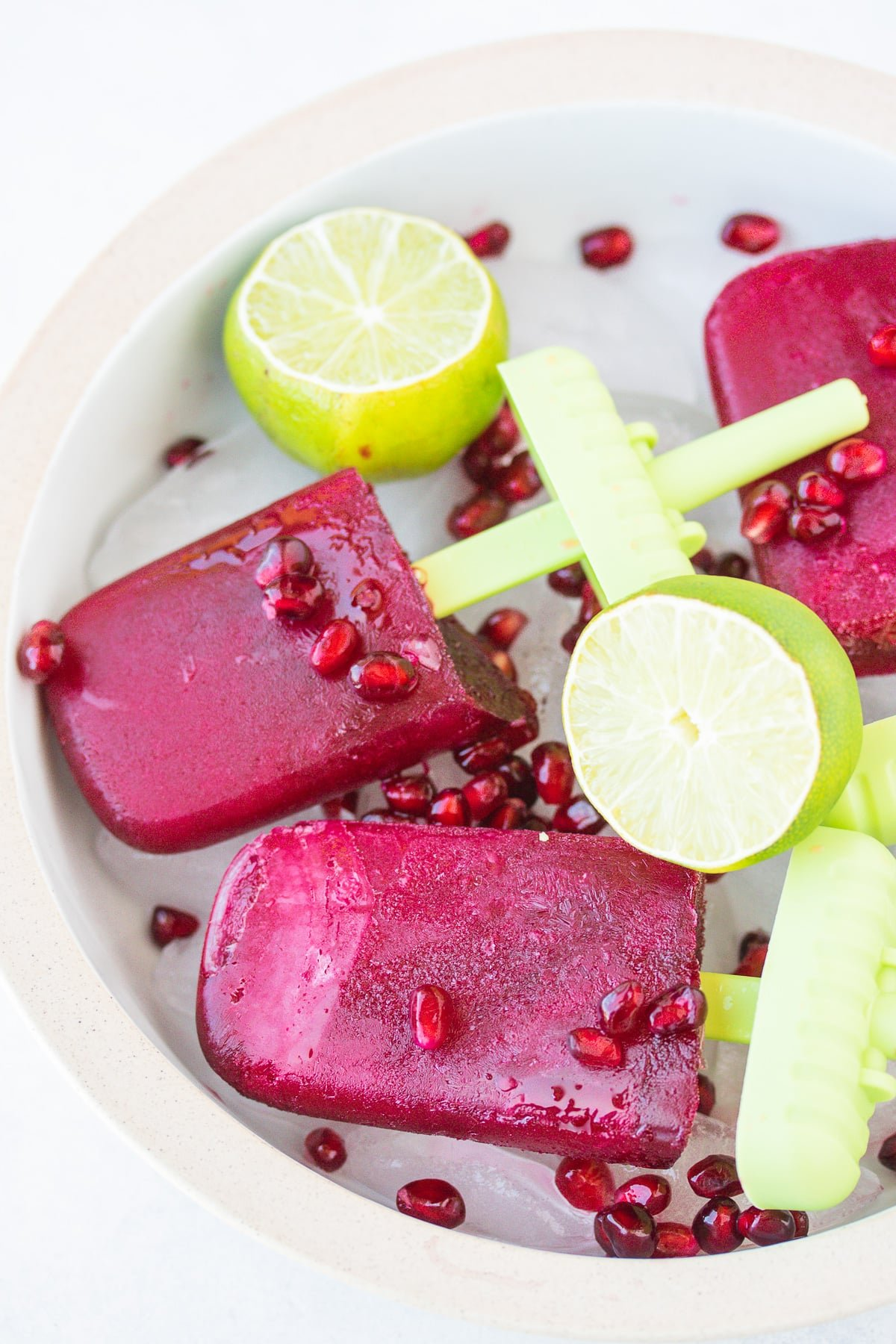 bowl of popsicles with pomegranate seeds and fresh limes