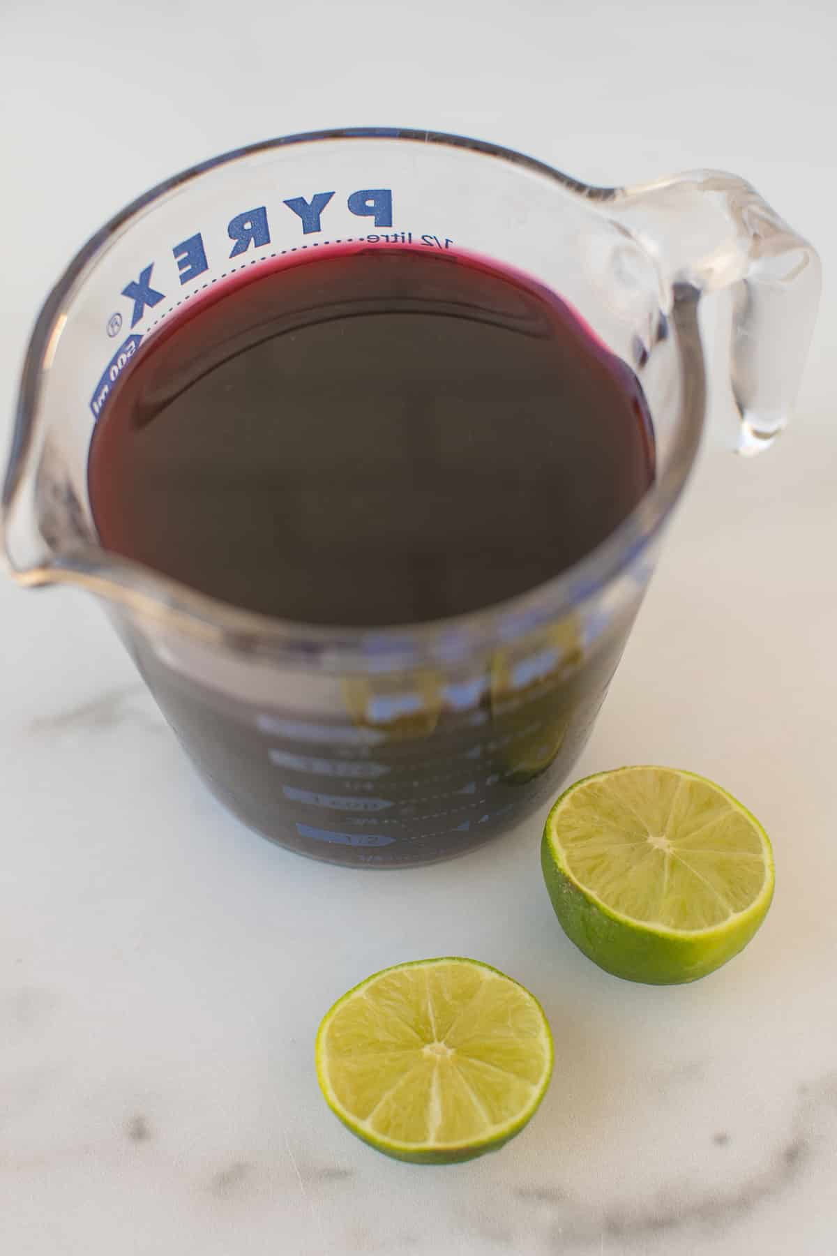 pyrex jar filled with pomegranate juice plus a lime