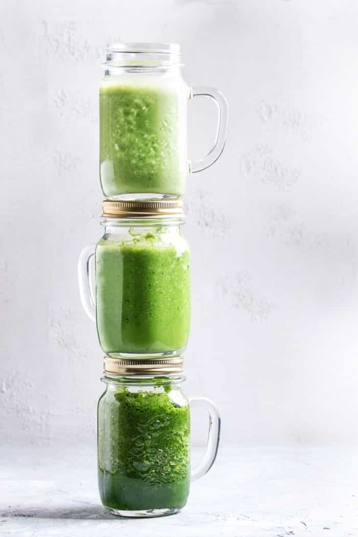 three jars of green smoothies stack on top of each other