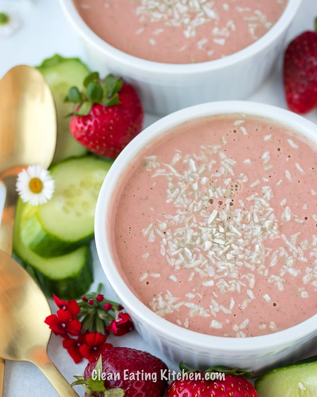 chilled vegan strawberry cucumber soup with gold spoons and flowers