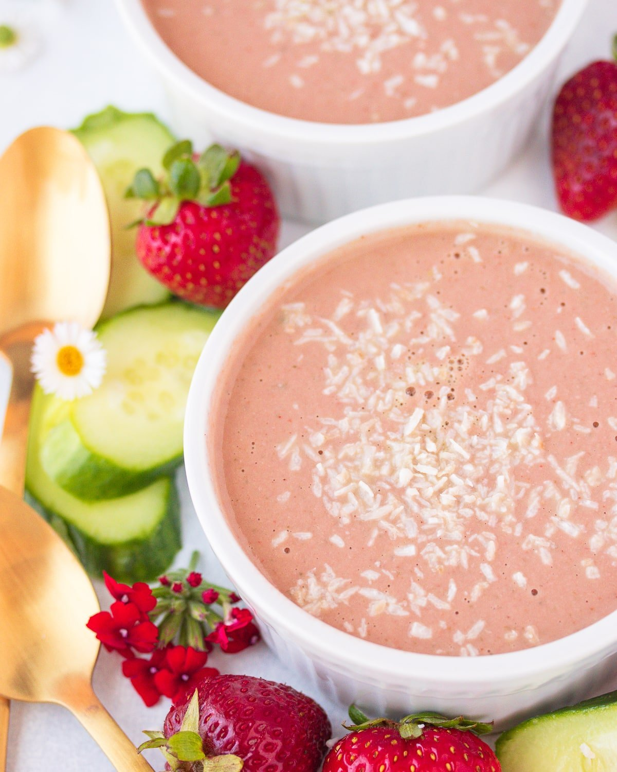 two bowls of strawberry soup with shredded coconut on top