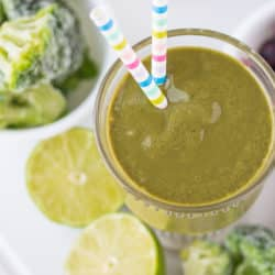 glass of green smoothie with a striped straw