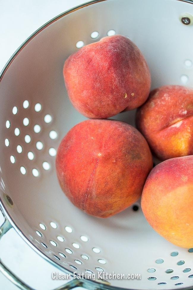 peaches in white colander