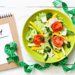 diet notebook on a table with a salad and a measuring tape