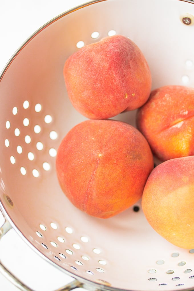 fresh peaches in a white colander