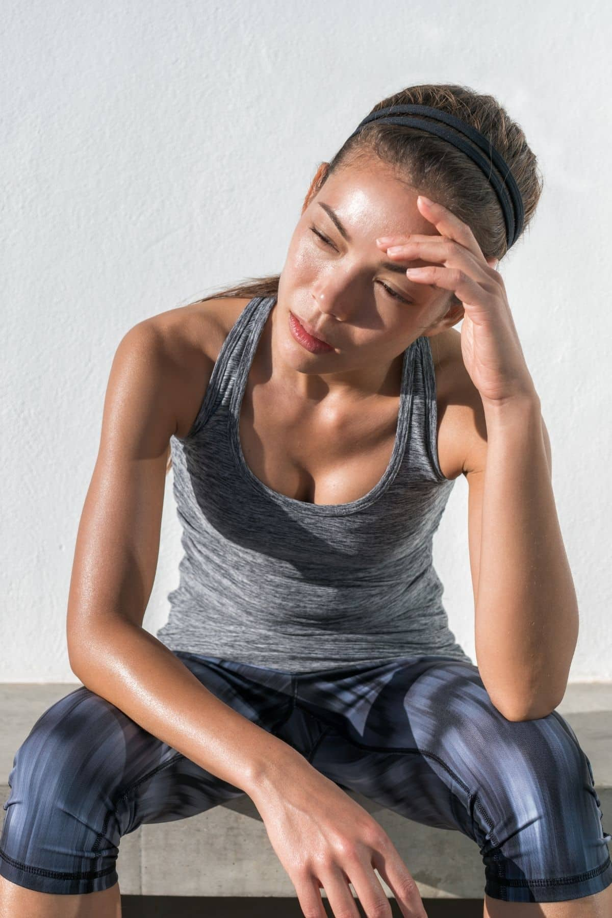 skinny woman in exercise clothes tired