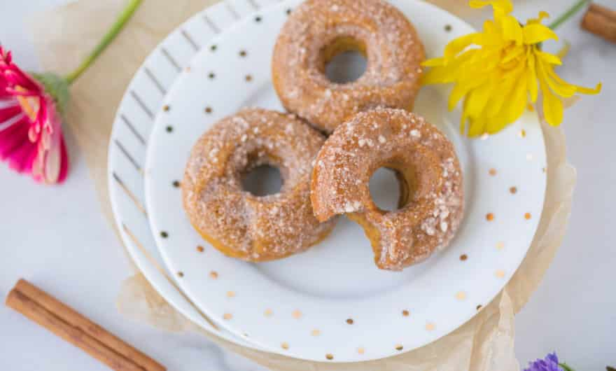 three baked pumpkin donuts on a white plate
