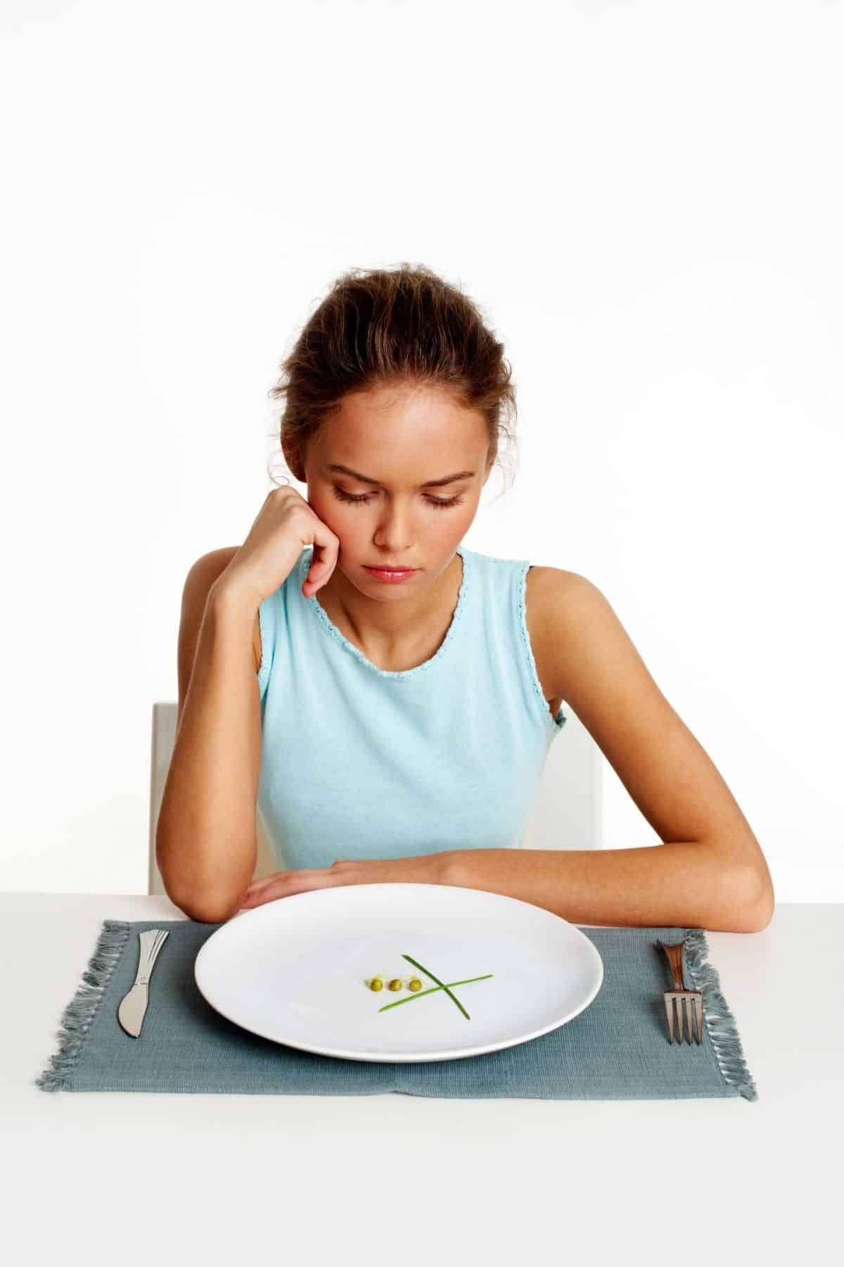 woman sitting in front of a plate with just a little bit of food on it