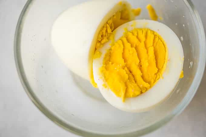 instant pot hardboiled egg cut in half in a glass bowl