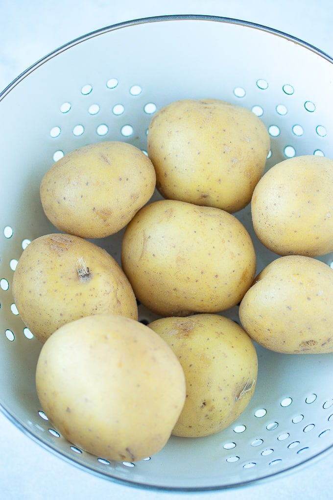 white potatoes in a white colander to be rinsed