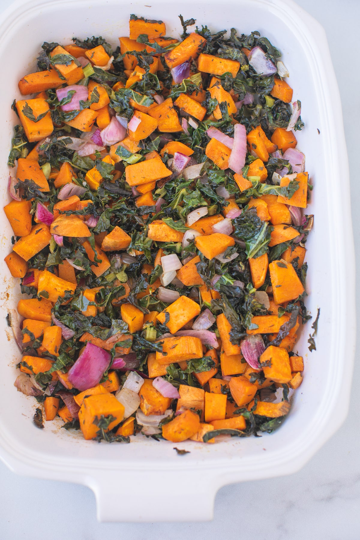 casserole dish with baked sweet potatoes and kale