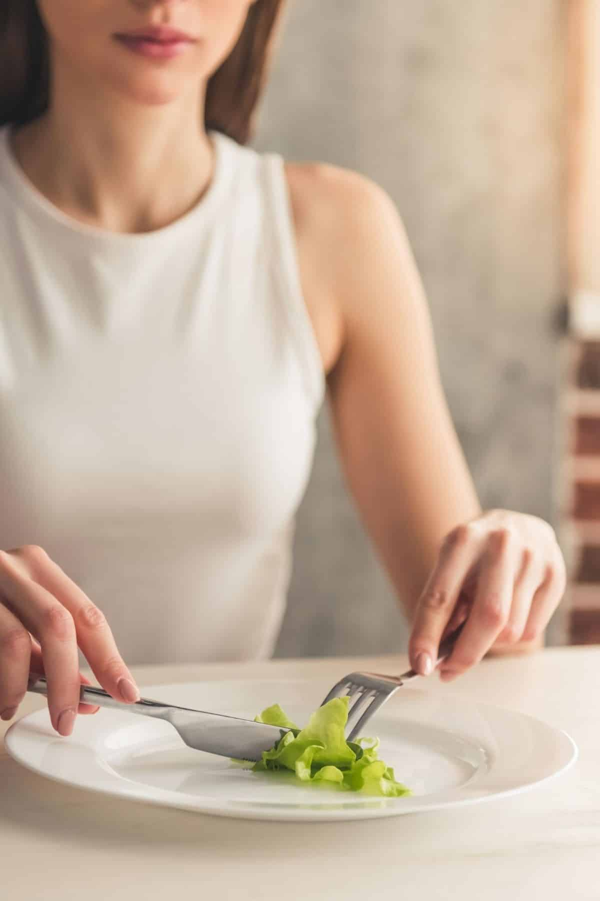 woman with eating disorder cutting a piece of lettuce