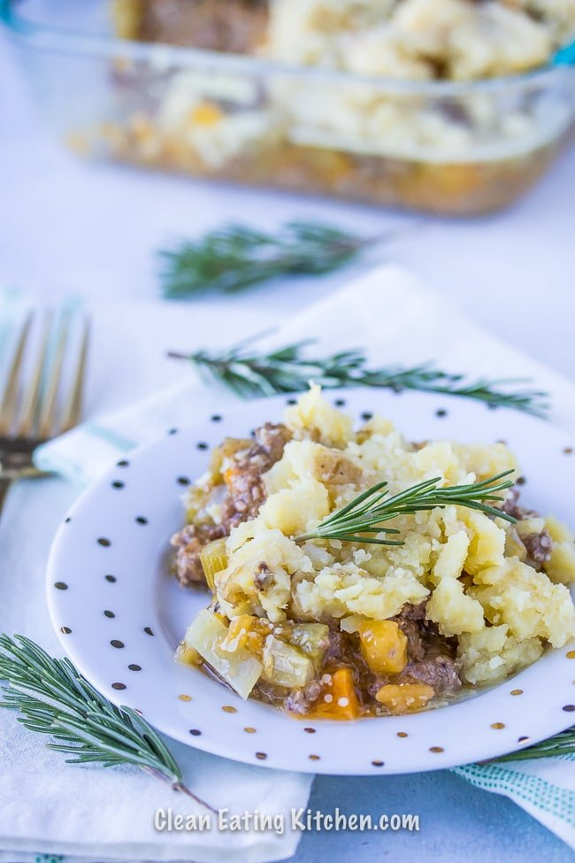 cottage pie on white plate with rosemary sprigs and a gold fork