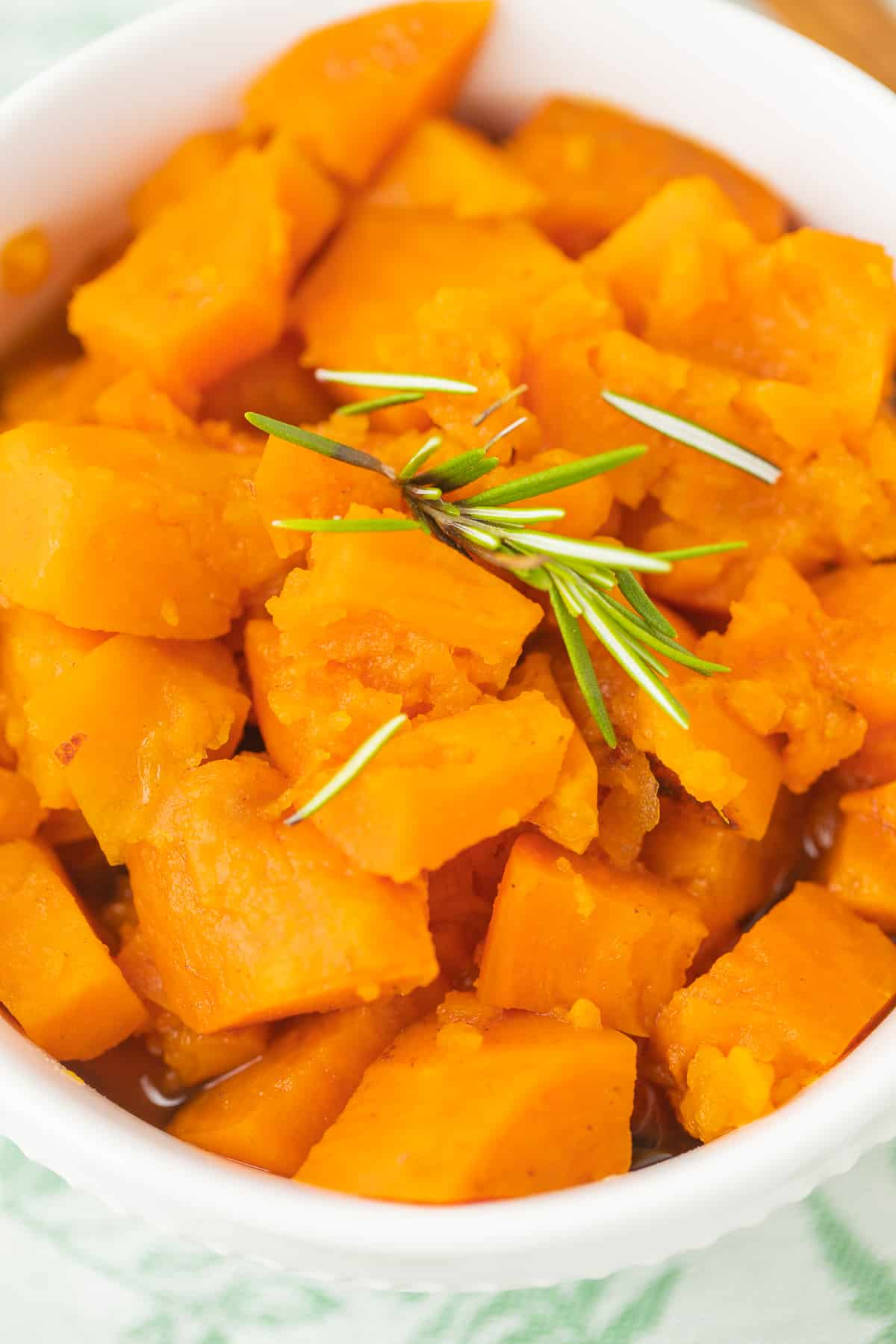 bowl of candied yams with rosemary on top