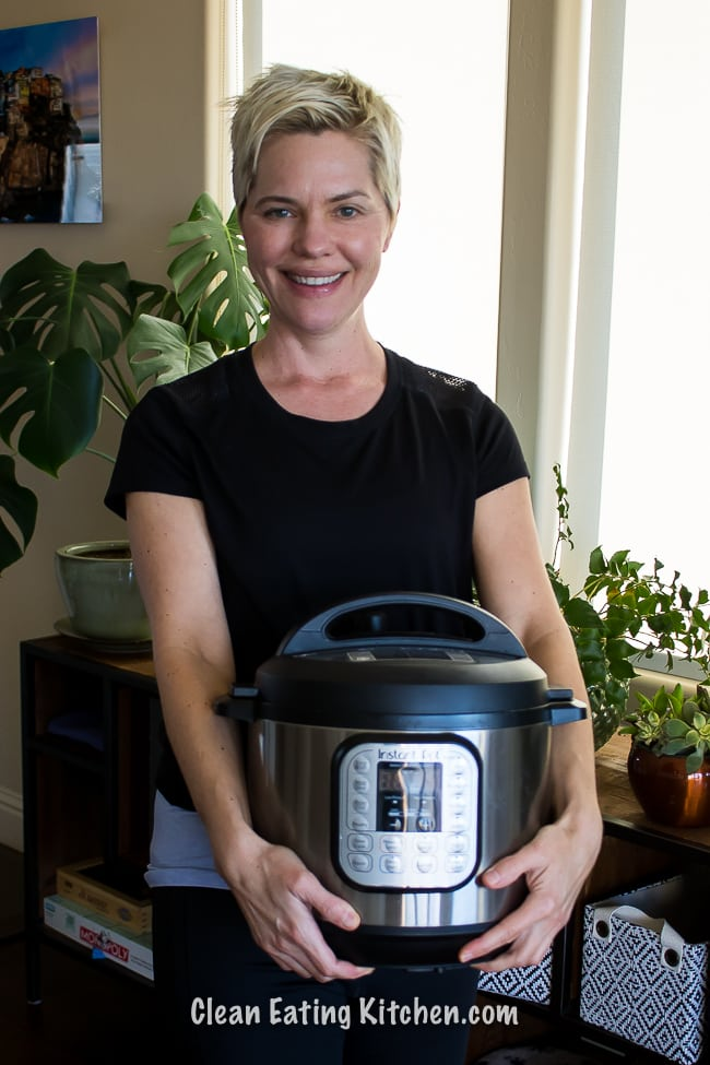 carrie holding instant pot with plants in the background