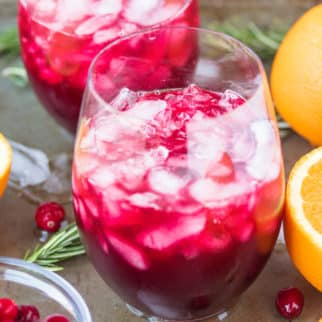 two glasses of pomegranate cranberry mocktail served with fresh orange slices