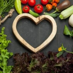 Fresh vegetables and heart. Diet, healthy lifestyle on a black background