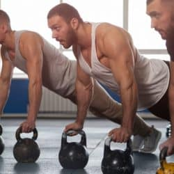 three men doing pushups with kettlebells