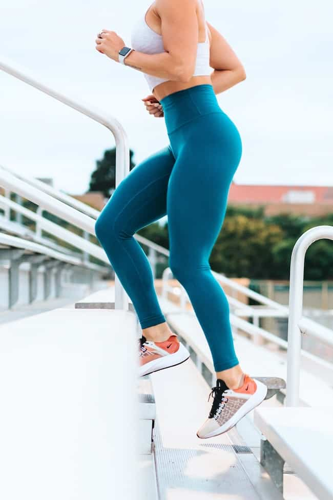 woman in blue leggings running up stairs