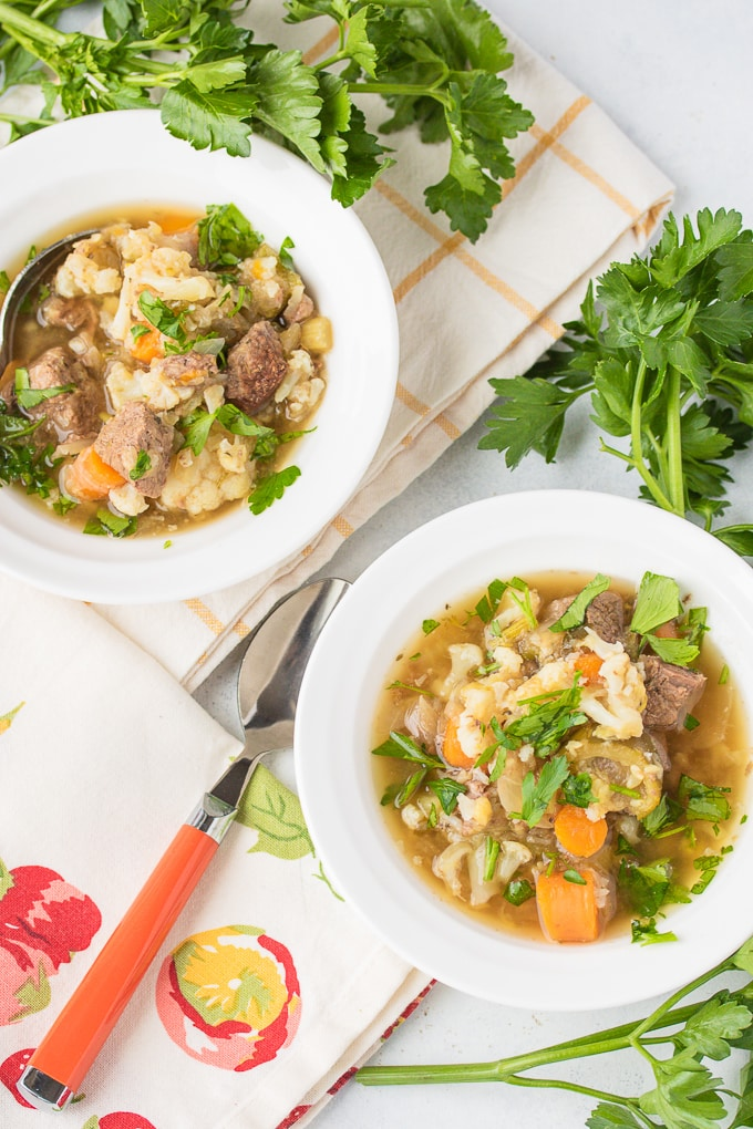 instant pot beef stew in two bowls with parsley